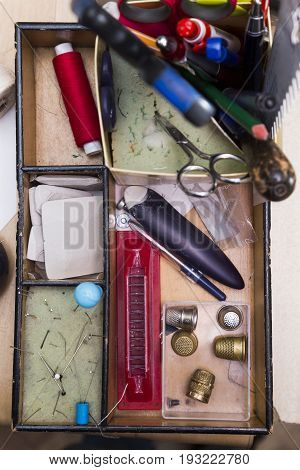 Box with compartments for devices for sewing clothes and creating sketches. In the box lie pen, pencil, scissor, laney, awl, needle, string, elastic band and thimble.