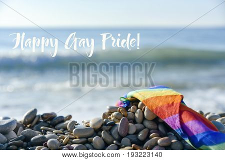closeup of a rolled rainbow flag in a shingle beach, with the ocean in the background, and the text happy gay pride