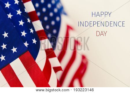 some american flags and the text happy independence day against an off-white background