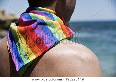 a young caucasian man seen from behind with a rainbow patterned handkerchief tied around his neck in front of the ocean