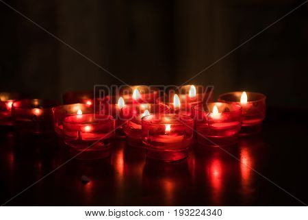 Red candles glowing in the dark. Taken in religious environment