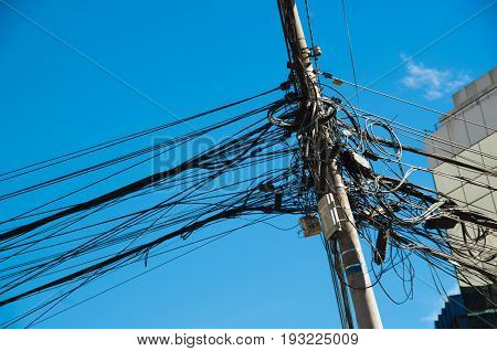 Close up of an entangled power lines in a an beautiful blue sky in the city of Quito.