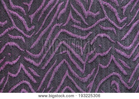 Knitwear fabric with purple abstract volume pattern. Part of a dress