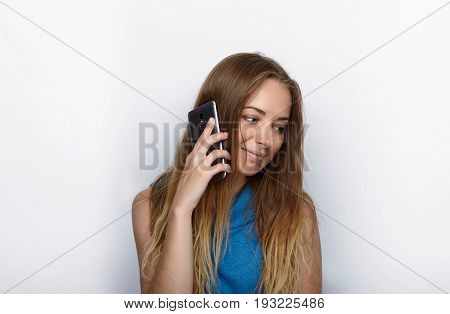 Headshot Of Young Adorable Blonde Woman With Cute Smile On White Background Texting On Her Smartphon