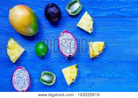 Pieces of thai fruits. Dragonfruit, mangosteen, mango, kiwi and lime on blue wooden background top view.