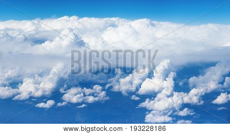 Panoramic view of the massif of the cumulus clouds like a mountains at the height of 10000 meters (about 6 miles) symbolizing purity and a heavenly dwelling place.