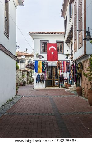 KUSADASI, TURKEY, 27TH FEBRUARY 2017 - Street in Kusadasi Turkey with Turkish flag and shop selling pashminas and scarves