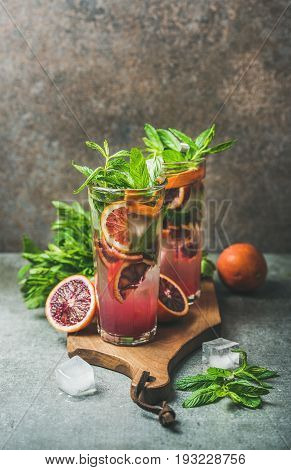 Blood orange citrus lemonade with mint and ice in tall glasses on wooden board over dark brown stone background, copy space. Refreshing summer drink concept