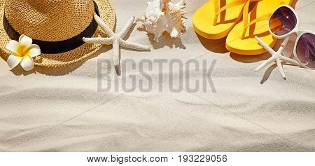 Straw hat,flip-flop and sunglass on sand beach