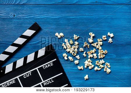 Watching the film. Movie clapperboard and popcorn on wooden table background top view.