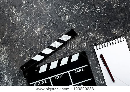 Work table of producer. Movie clapperboard and notebook on grey stone background top view copyspace.