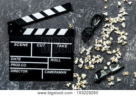 Watching the film. Movie clapperboard, sunglasses and popcorn on grey stone table background top view.