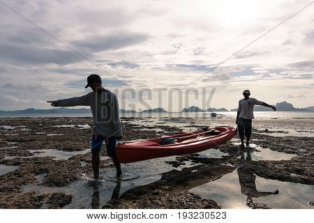EL NIDO, PALAWAN, PHILIPPINES - MARCH 29, 2017: Men briging back a kayak from the water to the beach at Las Cabanas Beach.