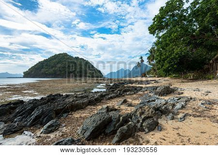 EL NIDO, PALAWAN, PHILIPPINES - MARCH 29, 2017: Rocky beach with some trees at Las Cabanas Beach.