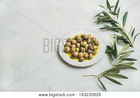 Pickled green Mediterranean olives in virgin olive oil on white ceramic plate and green olive tree branch over grey marble background, selective focus, copy space, horizontal composition