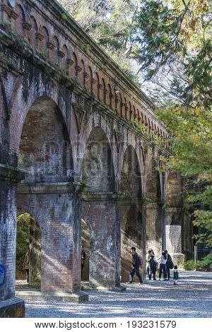 KYOTO JAPAN -NOV 20 2015: The tourists at the Suirokaku brick ancient aqueduct in Kyoto. This aqueduct was constructed in 1889 to carry water and goods between Kyoto and Lake Biwa