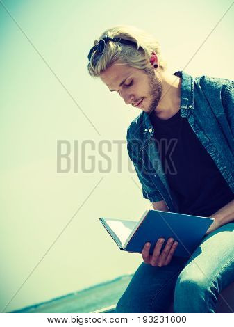 Holiday outdoor leisure time introvert relaxation concept. Sitting hipster man wearing jeans outfit reading book outside on sunny day sea in background