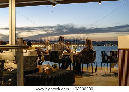 Young couple having dinner at a restaurant by the sea at night