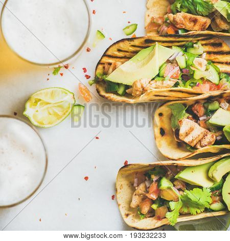 Healthy corn tortillas with grilled chicken fillet, avocado, fresh salsa, limes, beer over light grey marble background, top view, square crop. Healthy food, gluten-free, dieting, weight loss concept