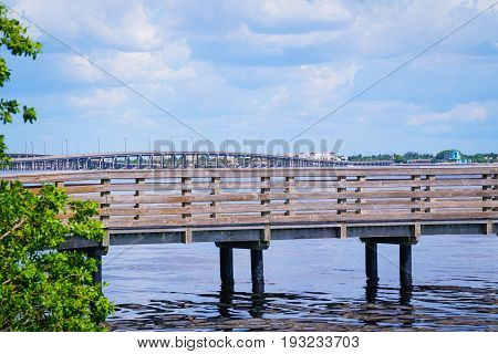 The Tamiami Trail bridge beyond the fishing pier goes over Charlotte Harbor and connects Port Charlotte with Punta Gorda.