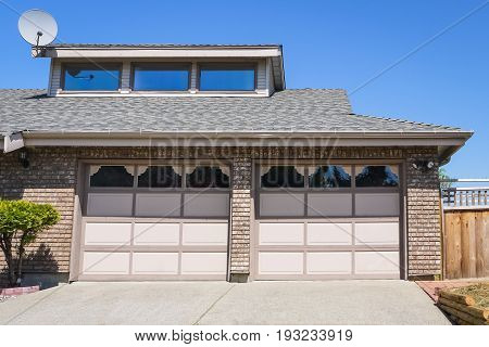 Two car garage with double door and concrete driveway in front