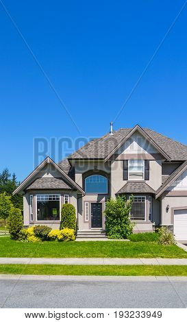 Luxury residential house on a street. Family house with landscaped front yard and pawed pathway in front
