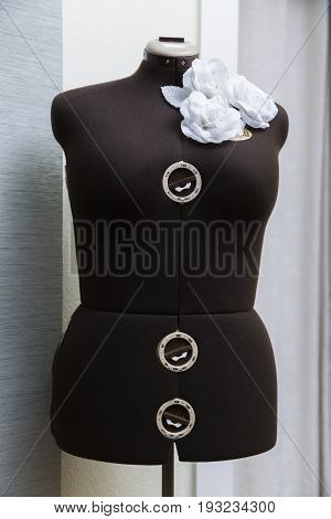 Female lady valet mannequin without head made of a black fabric with adjustable sizes with an ornament from three white artificial plastic roses with leaves on a shoulder on a white wall in atelier.