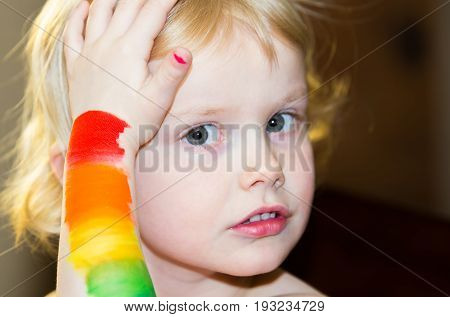 A close up of four year old girls' face holding arm up to her hair with a rainbow of colors painted on her arm