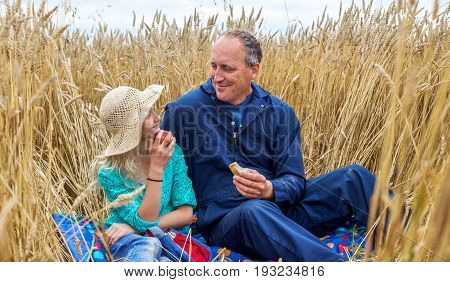 A father and his young daughter sitting on a blanket in a wheat field having a picnic