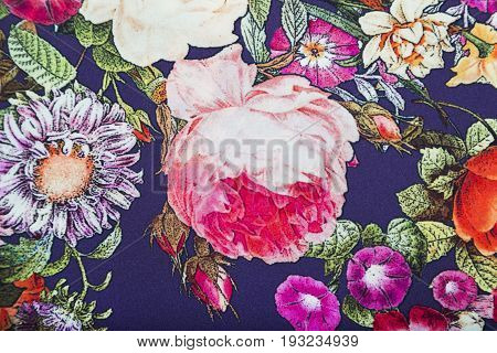 Staple viscose fabric with floral colorful abstract pattern of blue, green and yellow flowers and leaves.