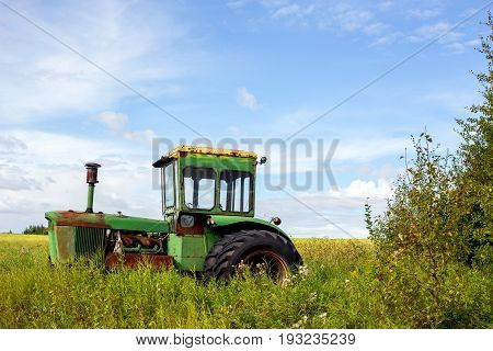 A vintage old green tractor abandoned beside a canola field in a cloudy rural landscape