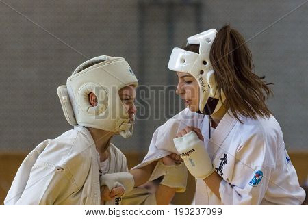 BERLIN - MARCH 18 2017: Girls-fighters in protective helmets during a fight close-up. European championship Kyokushin World Union (KWU) for Children and Youth.