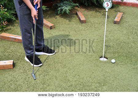 Boy Playing In Minigolf