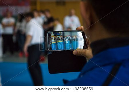 BERLIN - MARCH 18 2017: The spectator removes the video of fight on the mobile phone. European championship Kyokushin World Union (KWU) for Children and Youth.