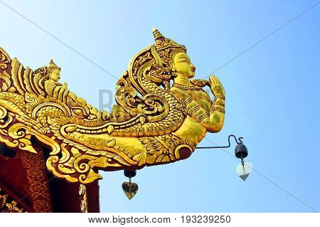 Native traditional Thai style angel carve on roof decoration and blue sky Golden Kinnaree act paying respect or sawasdee of Thailand The mythical half bird half woman