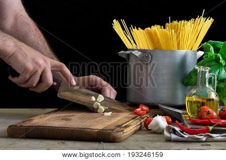 Man сooking an Italian pasta on a light wooden table