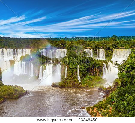 Several waterfalls from Iguazu Falls. Powerful two-stage waterfall creates rainbow and watery dust.  The concept of exotic and extreme tourism