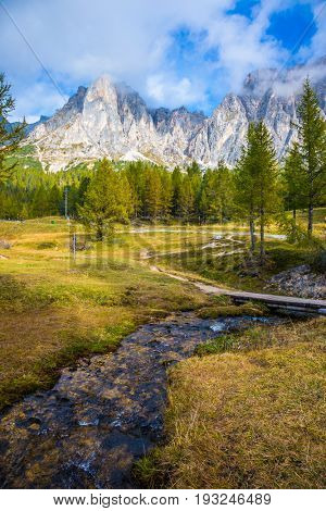 The concept of ecological tourism. Cold fast spring flows through the valley. The dizzying Dolomites. Sharp rocks surround the grassy valleys