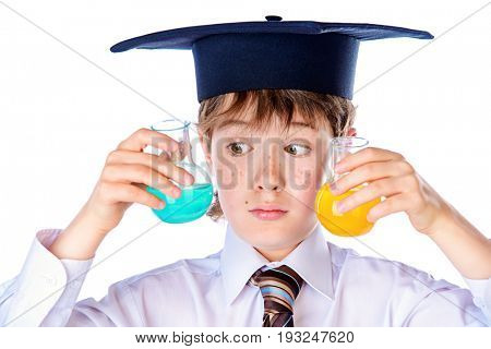 Smart student boy in white shirt, a tie and academic hat holds a flask with liquid. Educational concept. Isolated over white.