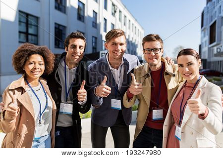 business, corporate and success concept - international group of people with name tags or conference badges showing thumbs up on city street