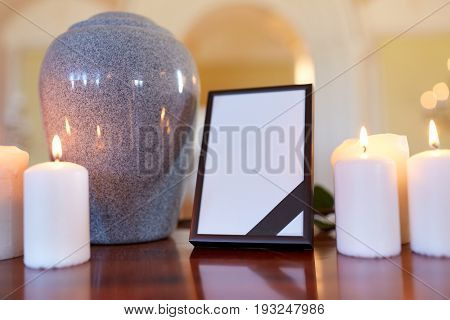 funeral and mourning concept - photo frame with black ribbon, cremation urn and burning candles on table in church