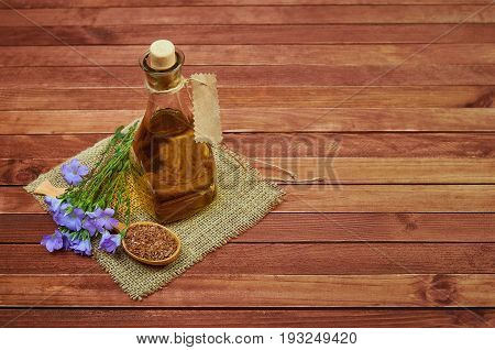 Flax Seeds In Wooden Spoon, Linum Plants With Flower And Linseed Oil On Glass Bottle