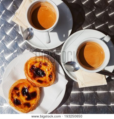 Pasteis de nata with coffee, typical Portuguese egg tart over dark background