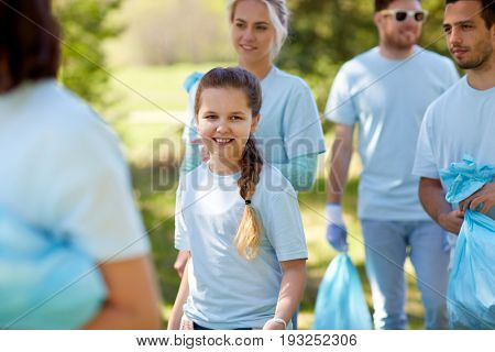 volunteering, charity, people and ecology concept - happy girl with group of volunteers cleaning garbage outdoors