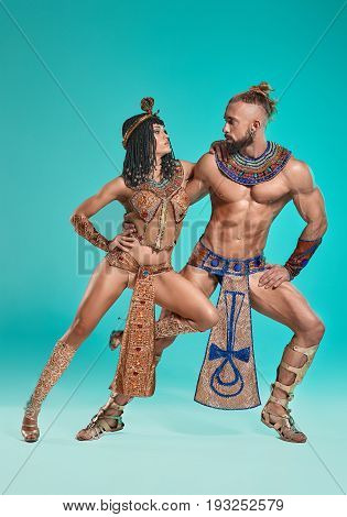 The man and woman in the images of Egyptian Pharaoh and Cleopatra on blue studio background