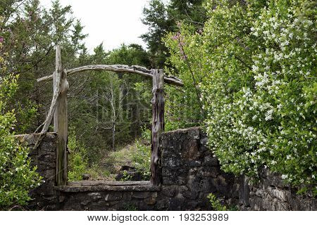 A stone wall with an arch way passage with flowers and bushes on the side of the path
