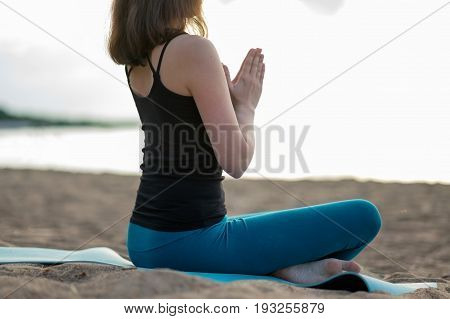 Woman doing yoga - meditating and relaxing in Padmasana Lotus Pose with palms together beach