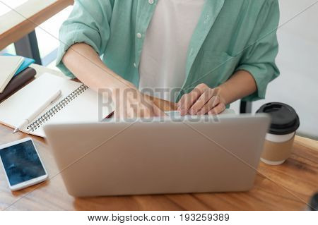 Asian hipster male with casual cloths typing on laptop computer keyboard while working in cafe on workday. Freelancer lifestyle and activity concept