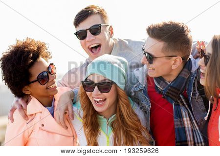 people, friendship and teenage concept - group of happy friends in sunglasses having fun and laughing outdoors