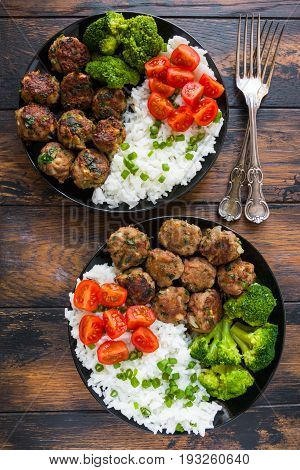 Fried meatballs with boiled white rice and broccoli on the black plates on the wooden rustic table top view.